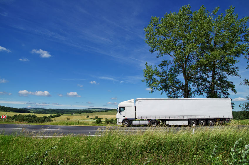 35791287 - rural landscape with white truck on the road, tall trees against the blue sky with white clouds